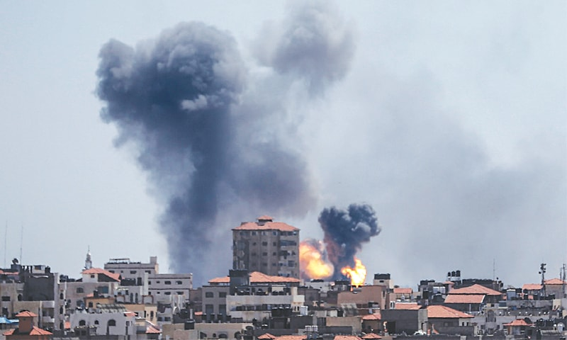 GAZA STRIP: Smoke billows from buildings after an air strike by Israel on Saturday.—AFP