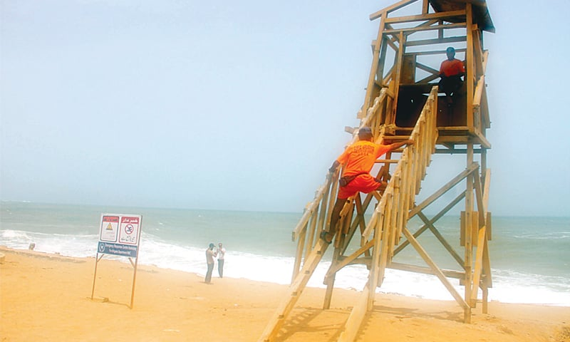 Lifeguards keep watch from their post, while a sign  warns beach visitors against swimming in the rough sea | White Star