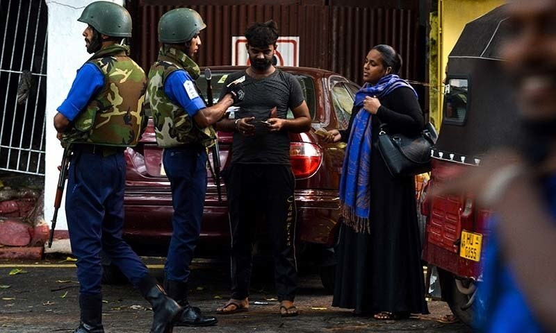 A Sri Lankan Muslim woman (R) looks on at a checkpoint in Colombo. — AFP/File