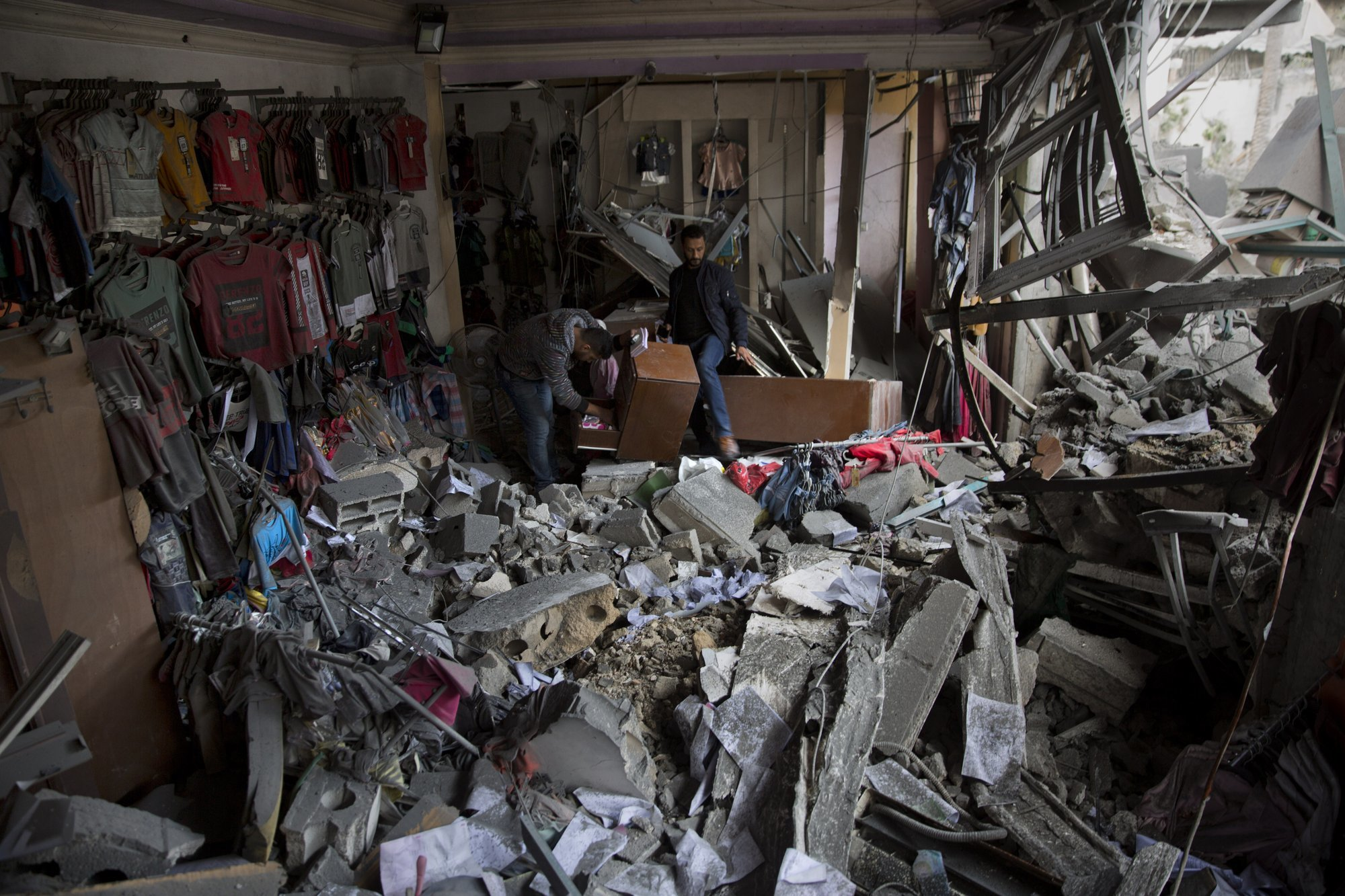 Two Palestinian men check the damage of their cloth shop following Israeli Airstrikes destroyed a multi-story building in Gaza City. ─ AP