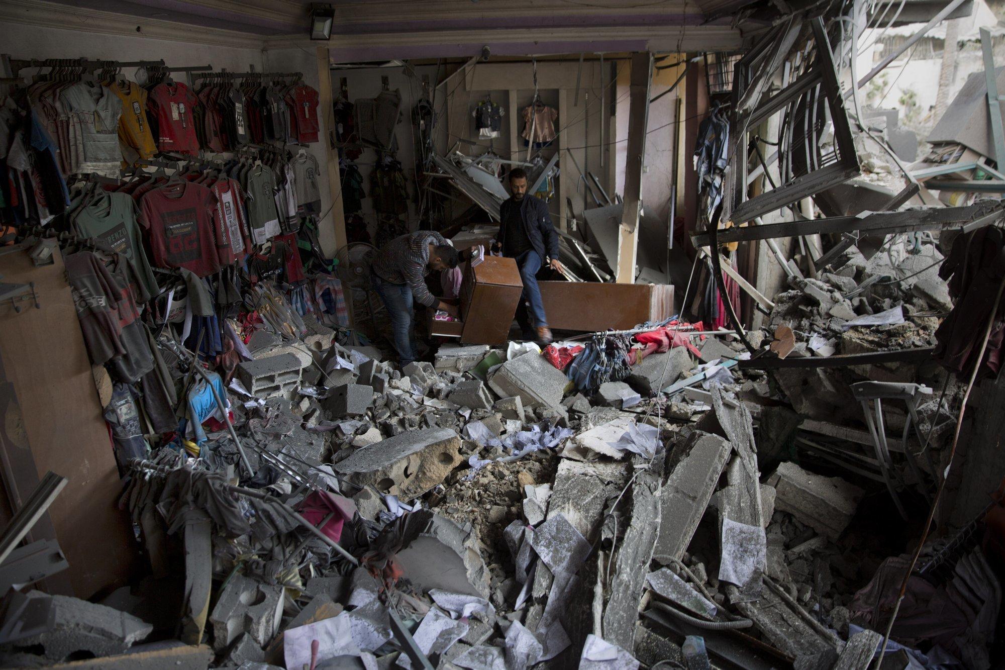اسرائیلی فوج کے فضائی حملے کے بعد دو فلسطینی اپنی کپڑوں کی تباہ حال دکان سے سامان نکال رہے ہیں، فوٹو: اے پی