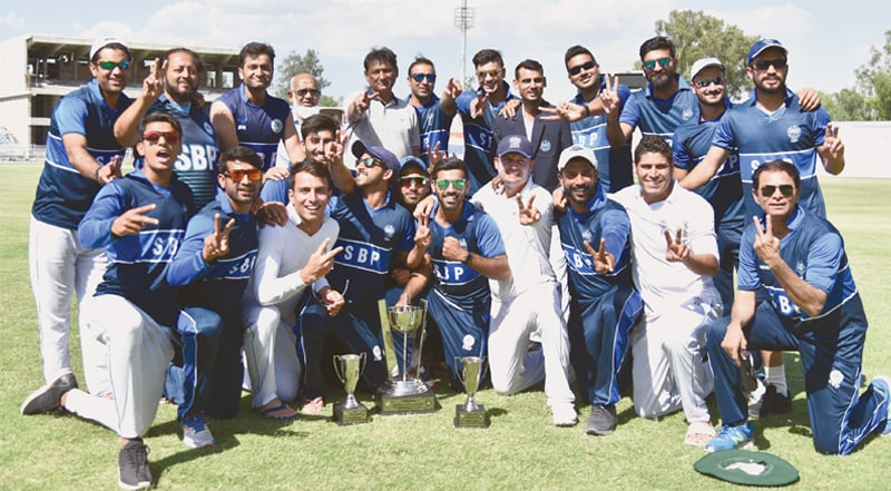 RAWALPINDI: The victorious State Bank squad members pose with the Patron's Trophy Grade-II trophy after winning the at the Pindi Cricket Stadium on Sunday.—Courtesy PCB