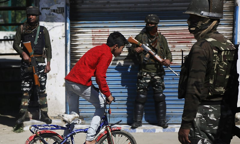 Indian paramilitary soldiers stand guard as a Kashmiri boy rides a bicycle outside a polling station in Pulwama. ─ AP