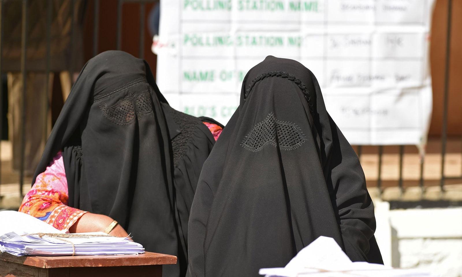 مقبوضہ کشمیر میں برقع پوش خواتین پولنگ ایجنٹس کے فرائض انجام دے رہی ہیں — فوٹو: اے ایف پی