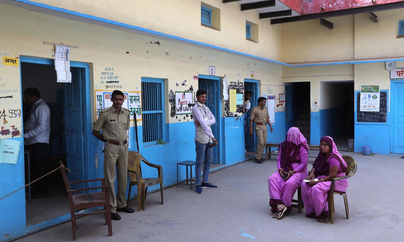 راجستھان میں آفیسرز اور سیکیورٹی اہلکار پولنگ کے لیے لوگوں کی آمد کا انتظار کررہے ہیں — فوٹو: اے پی