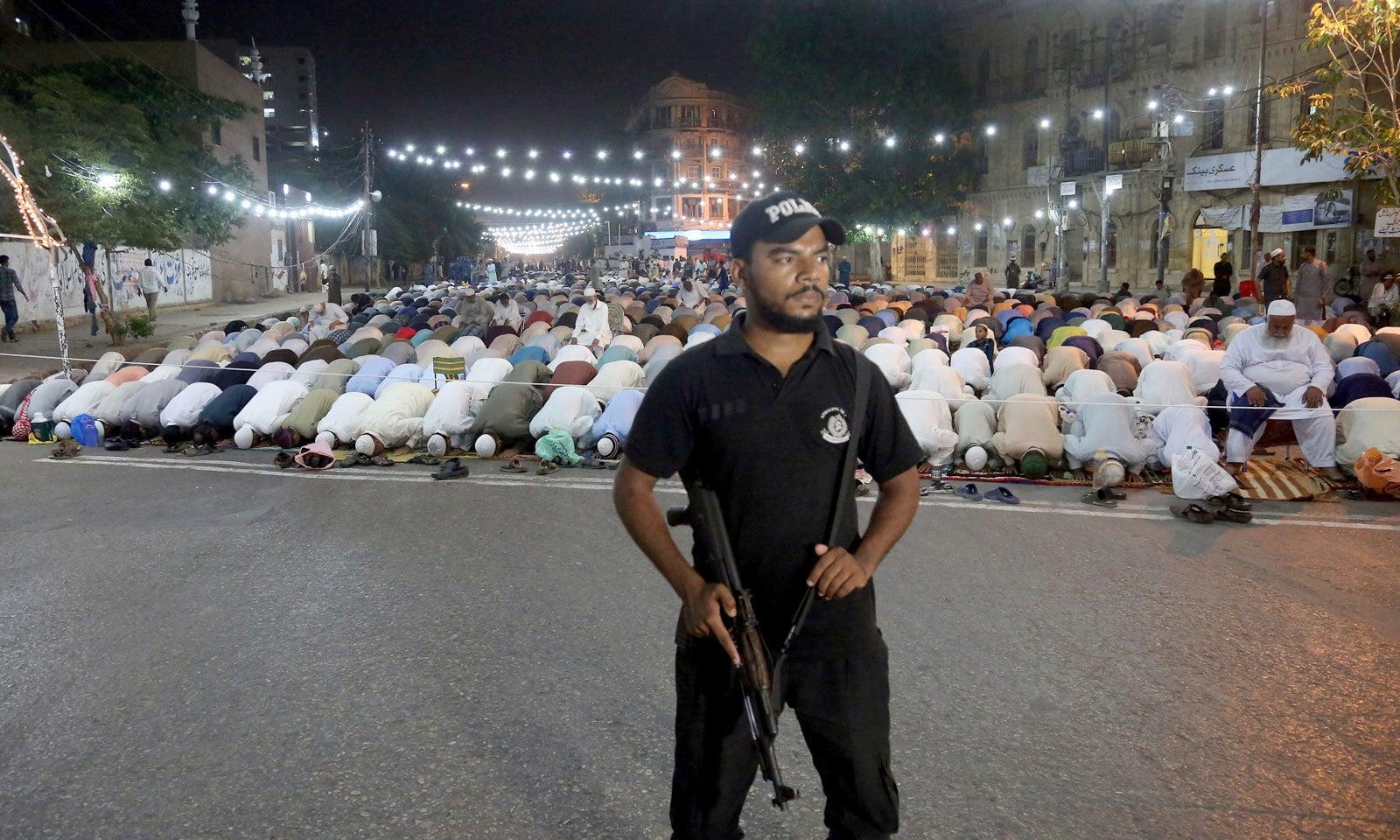 کراچی میں پہلی نماز تراویح کے دوران پولیس اہلکار الرٹ کھڑا ہے — فوٹو: اے پی