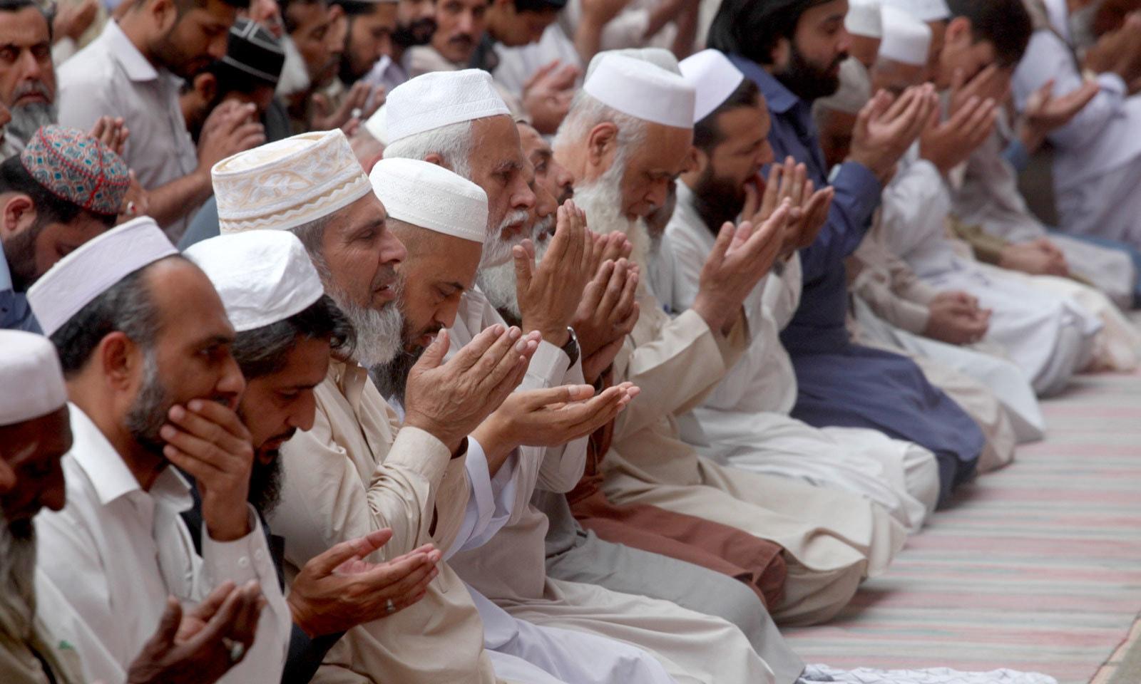 پشاور کی مسجد میں نماز تراویح کے بعد دعا مانگی جارہی ہے — فوٹو: اے پی