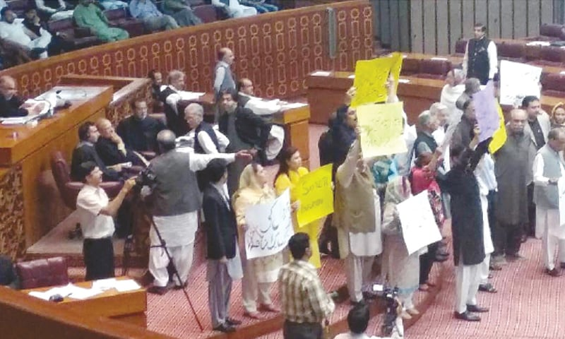 ISLAMABAD: Holding placards, members of opposition parties protest during the National Assembly's session on Monday.—INP