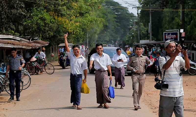 Reuters reporters Wa Lone and Kyaw Soe Oo gesture as they walk free outside Insein prison after receiving a presidential pardon in Yangon, Myanmar on May 7, 2019. — Reuters