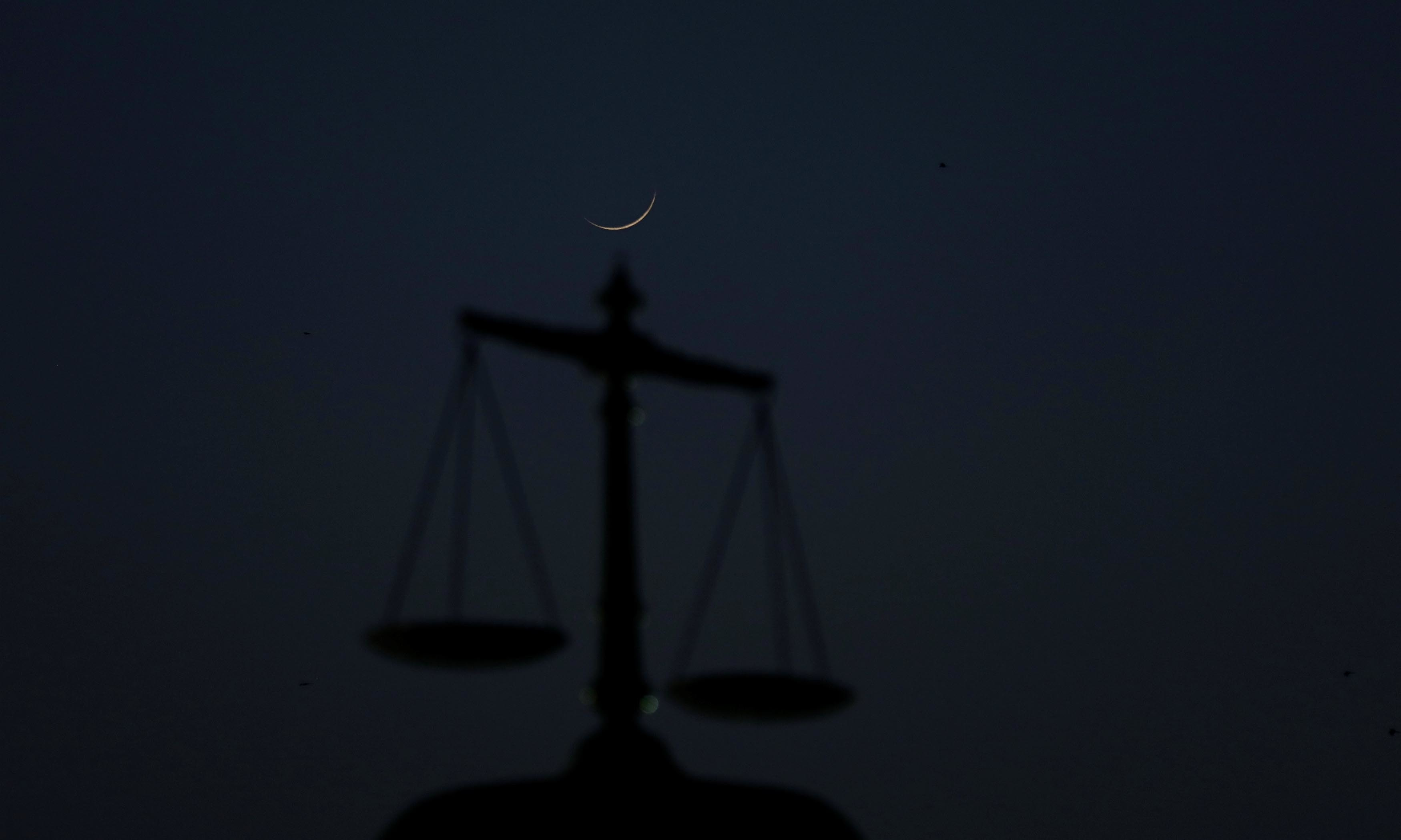 "The crescent moon is seen above the monument of balance scale at the Sindh High Court, as Muslims attend ""tarawih"" to mark the fasting month of Ramazan in Karachi. — Reuters"