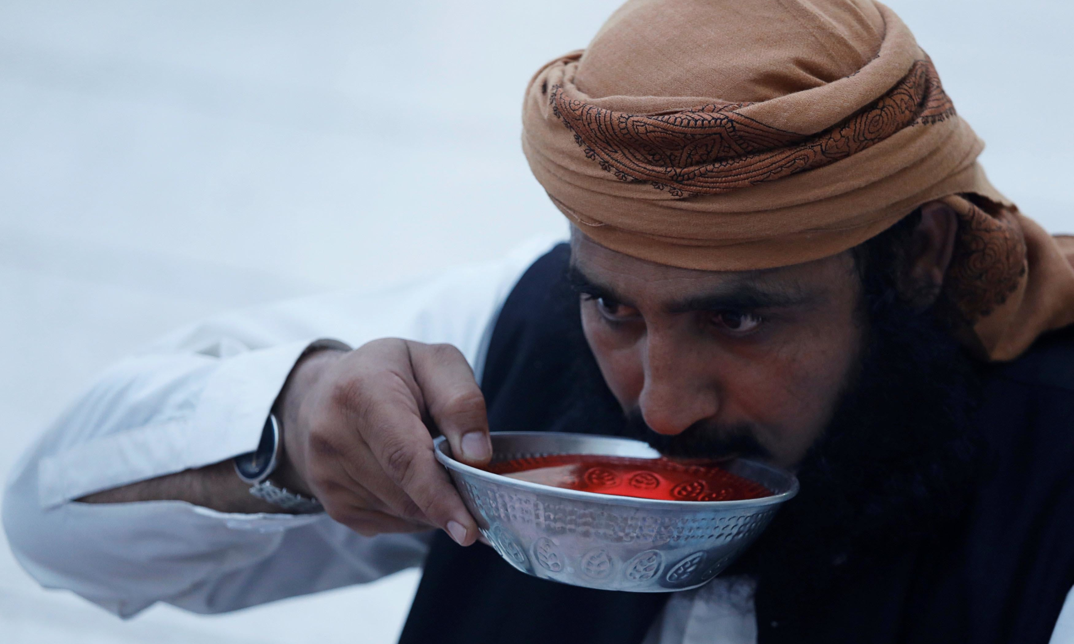 A man takes a sip from a bowl of syrup as he breaks his fast in Peshawar.— Reuters