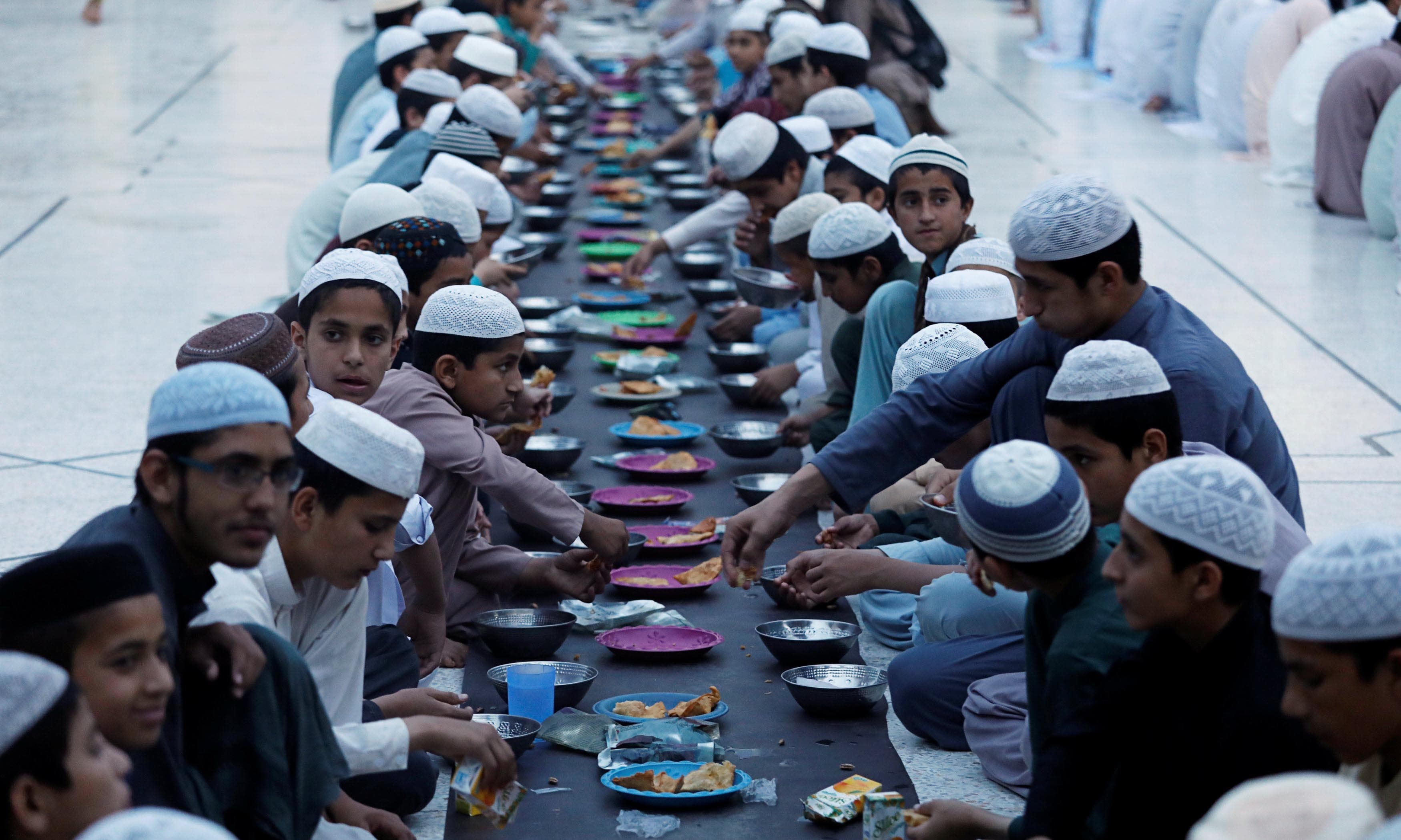 People eat as they break their fast in Peshawar. —Reuters