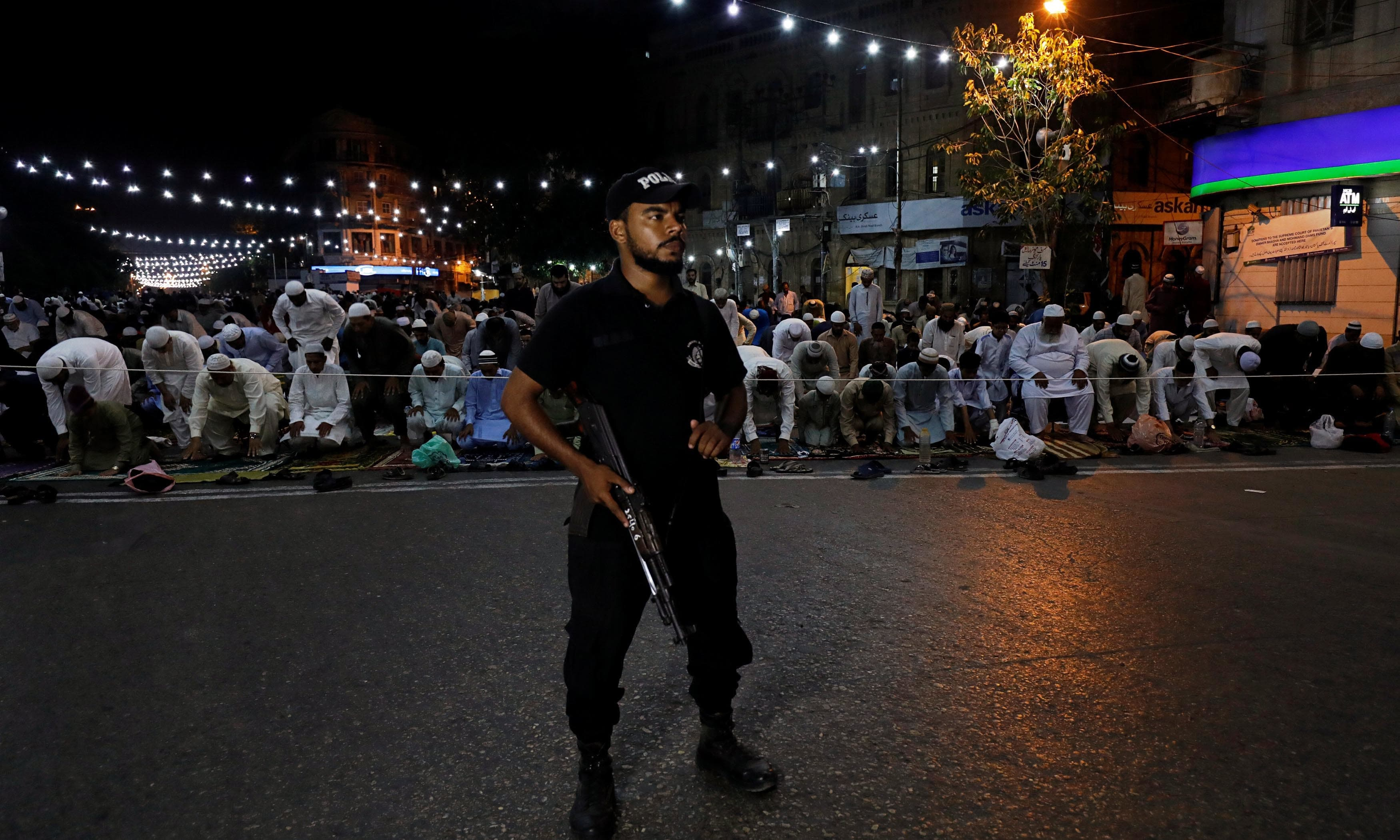 "A police officer stands guard as men attend ""tarawih"" along a road in Karachi. — Reuters"
