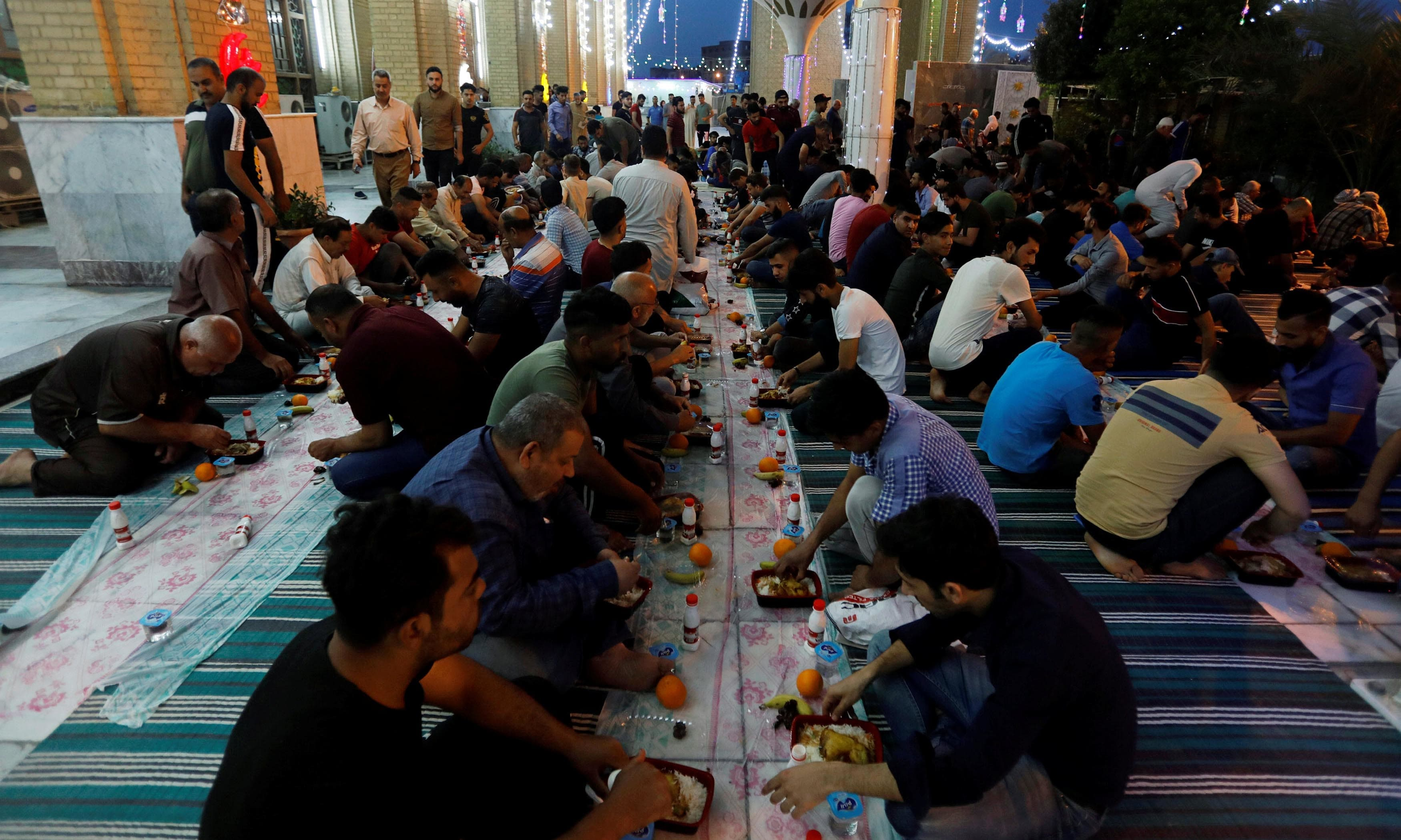 Iraqi Muslims eat after breaking their fast in a mosque during the holy Ramazan in Baghdad. — Reuters