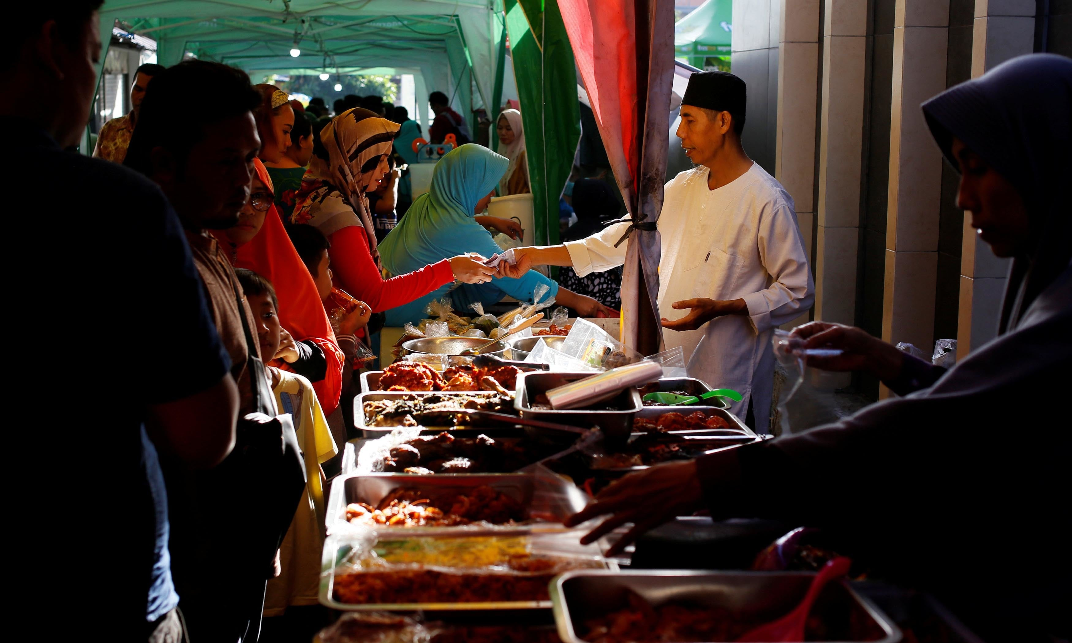 Indonesian Muslims buy food for iftar at a traditional food market during the first day of Ramazan in Denpasar, Bali, Indonesia. — Reuters