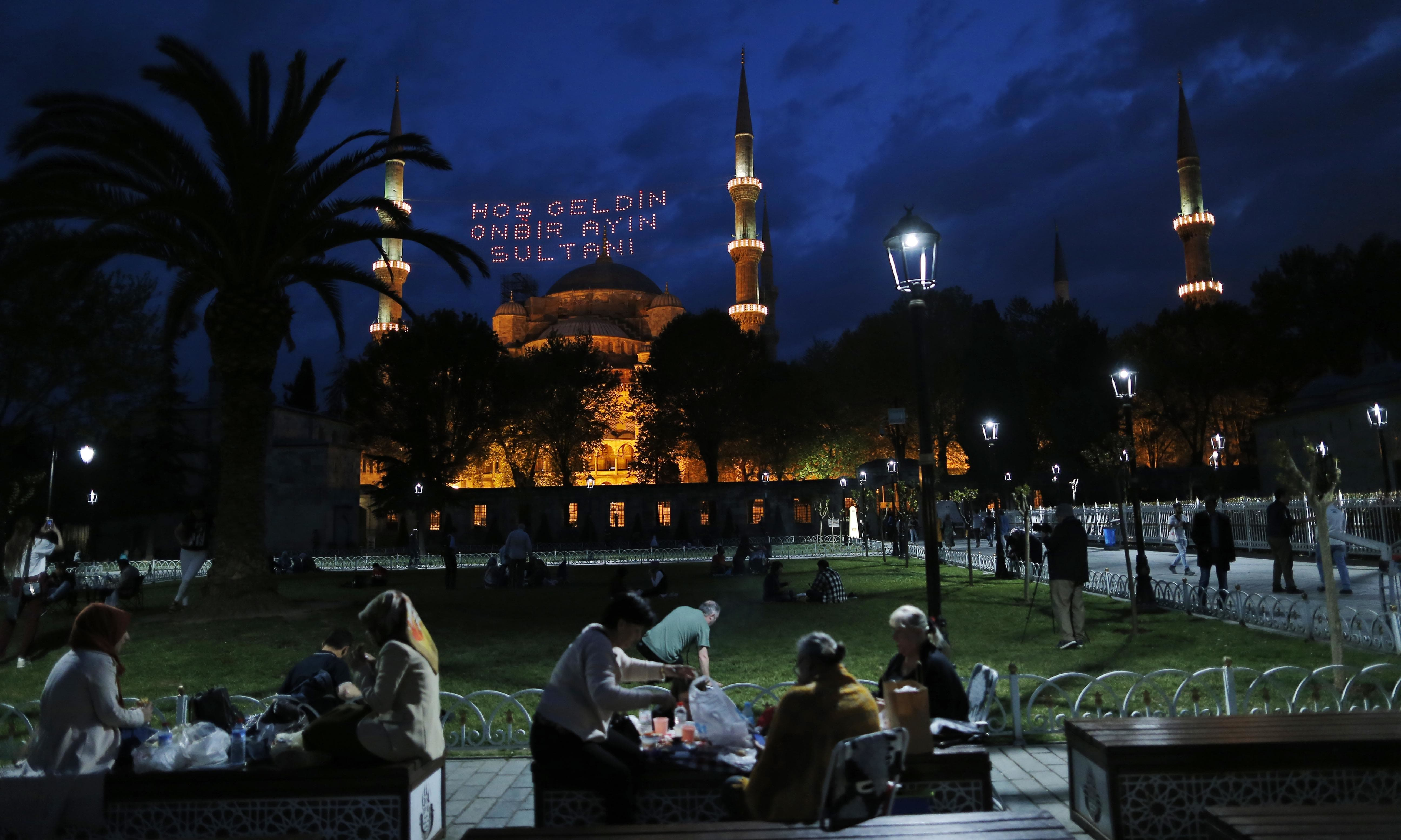 Backdropped by the iconic Sultan Ahmed Mosque, better known as the Blue Mosque, people break their fast in the historic Sultanahmet district of Istanbul. — AP