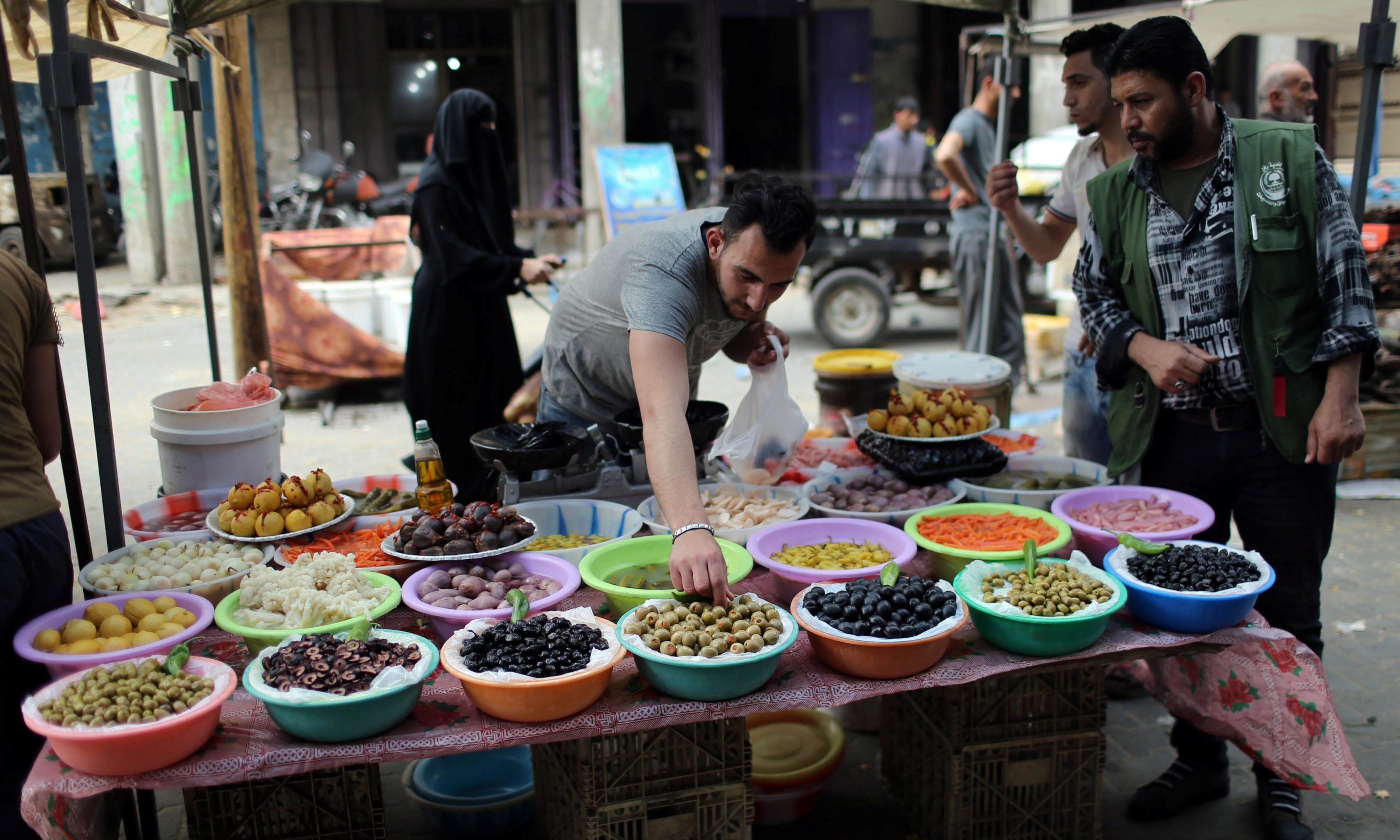A Palestinian man sells olives and pickles on the first day of  Ramazan, in the southern Gaza Strip. — Reuters