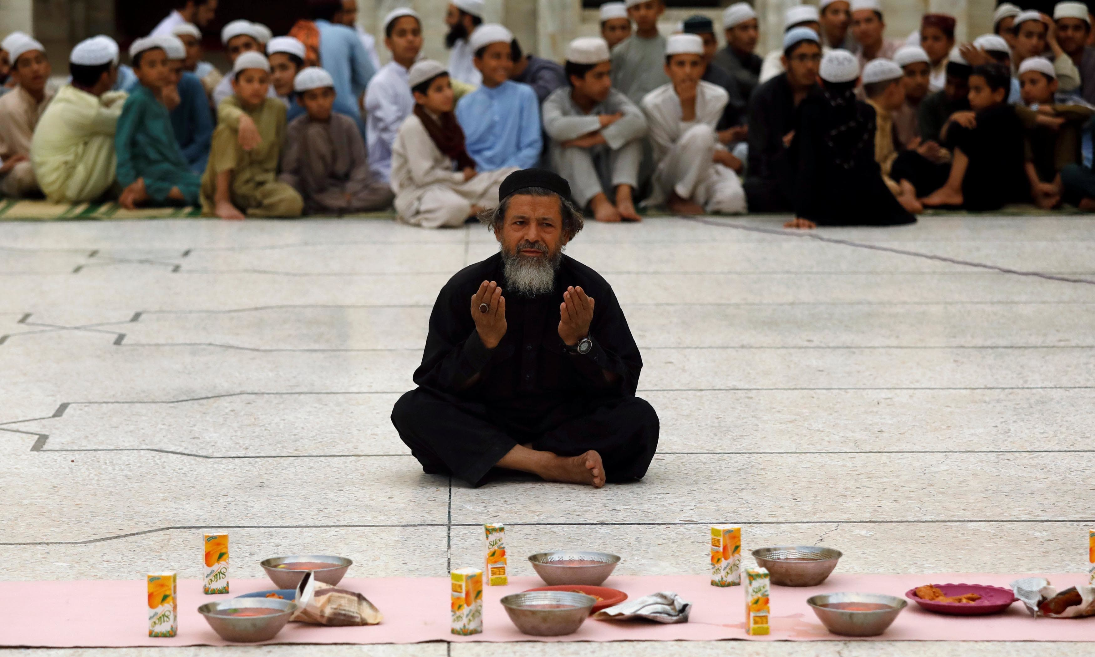 A man prays before breaking his fast during the fasting month of Ramazan in Peshawar. — Reuters