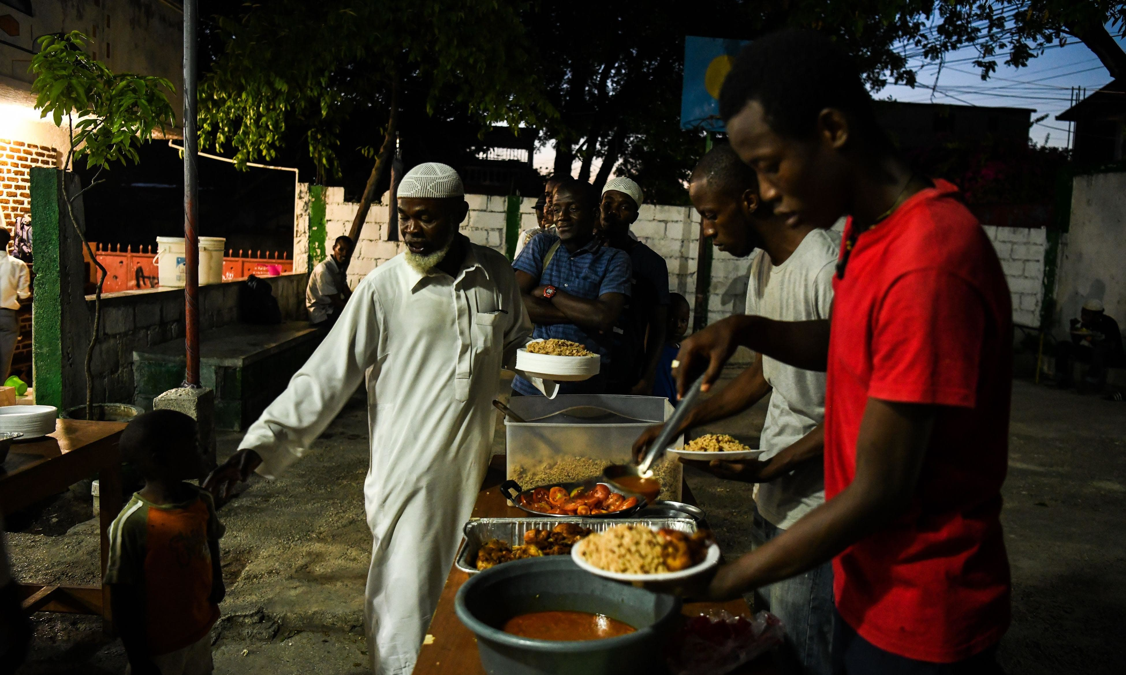 Muslim men stand in queue for food at iftar at the Masjid At-Tawheed mosque in Port-au-Prince in Haiti. — AFP