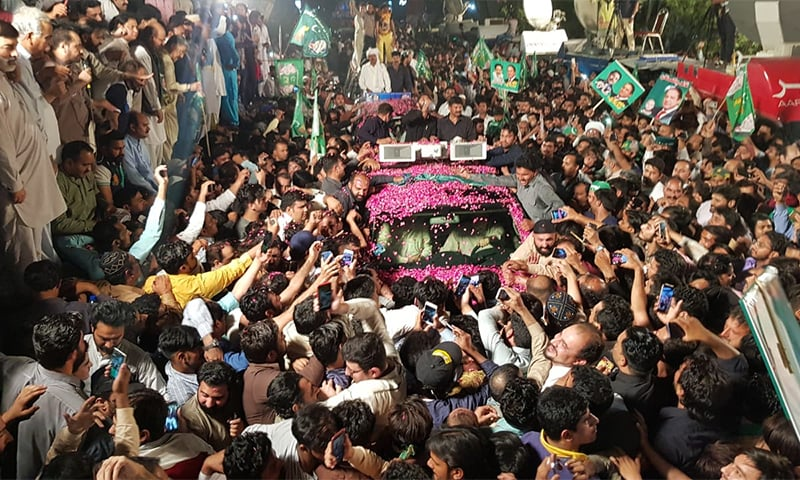 The convoy carrying Nawaz Sharif on the way to jail is surrounded by supporters. — Photo by Adnan Sheikh