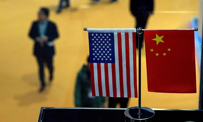 This file picture shows a Chinese and US flag at a booth during the first China International Import Expo (CIIE) in Shanghai. — AFP/File