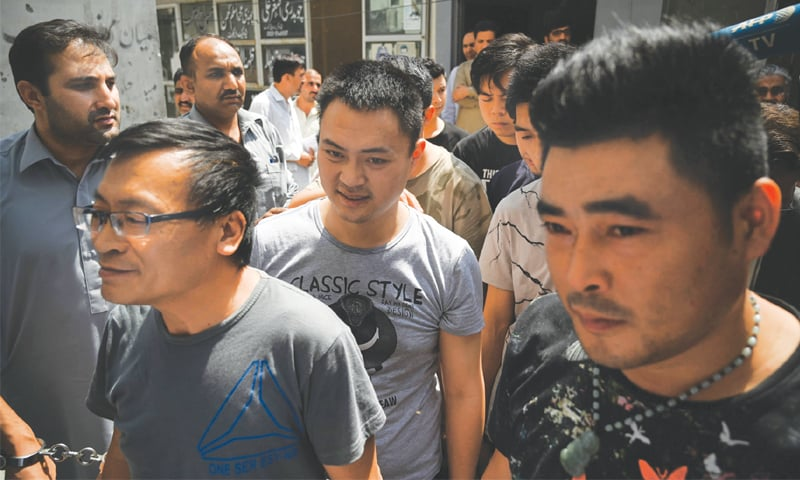 Detained Chinese nationals walk together as they arrive at a court after being arrested by the FIA in the bride trafficking case on Thursday.—AFP