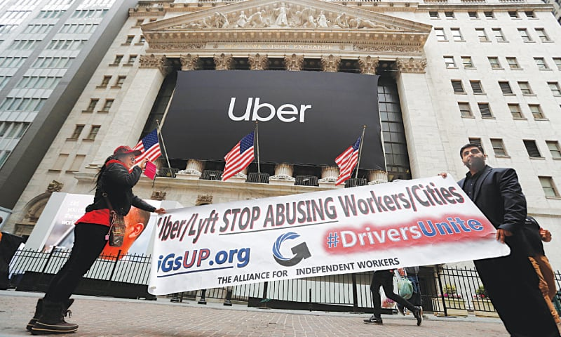 NEW YORK: Protestors display a banner outside the New York Stock Exchange (NYSE) as Uber Technologies Inc. holds it's IPO on Friday.—Reuters
