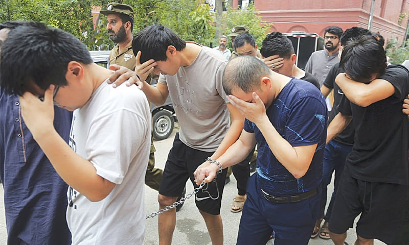 Lahore: Detained Chinese nationals, allegedly associated with a trafficking gang to lure Pakistani women into fake marriages, try to cover their faces while being escorted by Federal Investigation Agency officers to court on Saturday.—AP