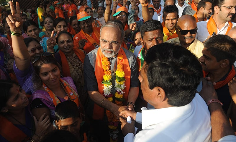 In this file photo taken on April 10, 2014, Indian businessman Vikas Mahante, a Modi lookalike, greets supporters at an election campaign event in Mumbai. ─ AFP