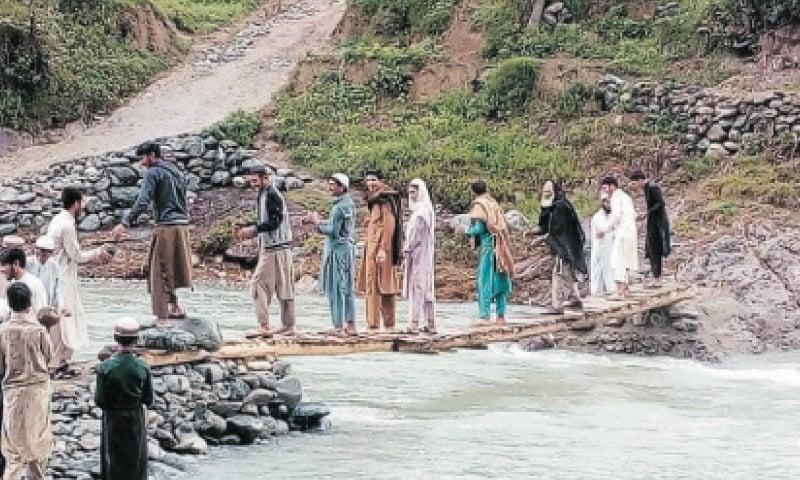 Locals repair a makeshift pedestrian bridge on Brawal River in Sro Manzai area of Upper Dir. — Dawn