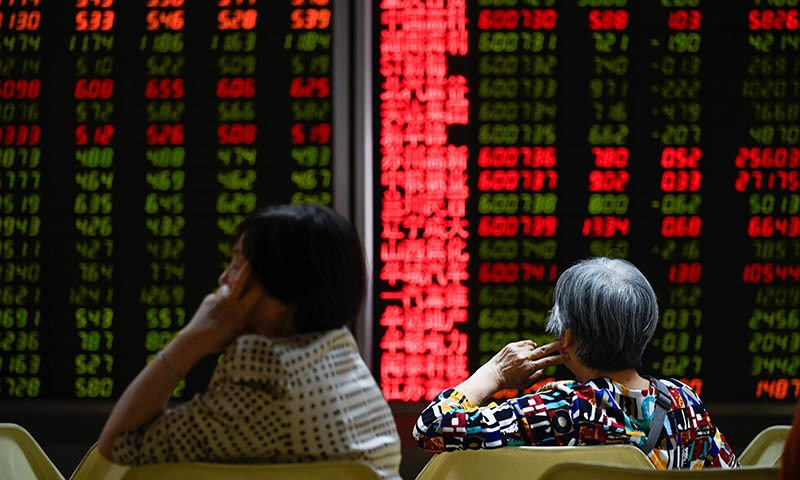 Investors rest on a chair in front of screens showing stock market movements at a securities company in Beijing on May 14, 2019. — AFP
