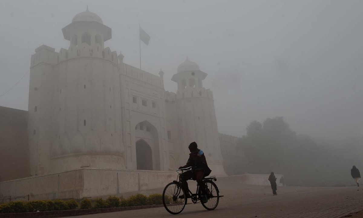 A cyclist rides past the Lahore Fort engulfed by dense fog | White Star
