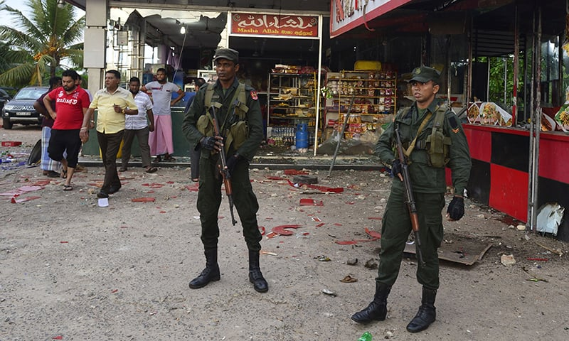 Sri Lankan security personnel stand guard outside a damaged shop after a mob attack in Minuwangoda on May 14, 2019. — AFP