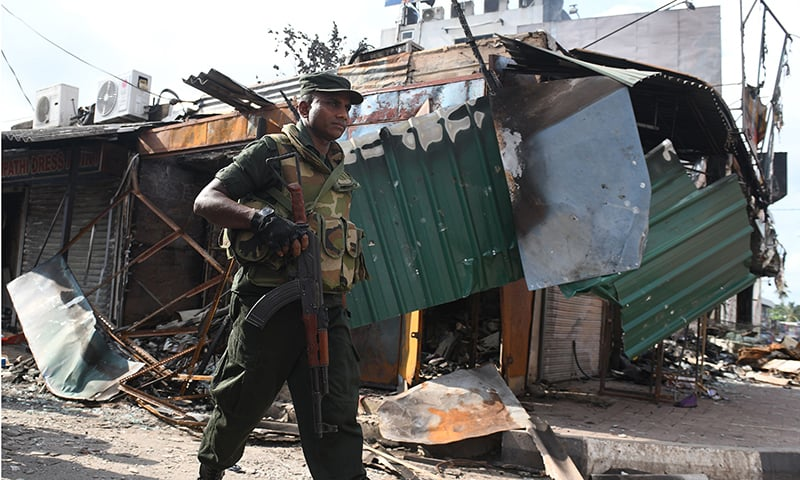 A Sri Lankan soldier walks past a damaged shop after a mob attack in Minuwangoda on May 15, 2019. — AFP