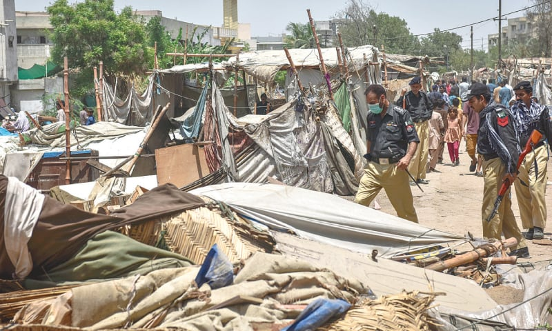 POLICE personnel patrol an area being cleared of encroachments in Gulshan-i-Iqbal's Block 13 on Wednesday while (right) a family stands where their abode once stood.—Fahim Siddiqi / White Star