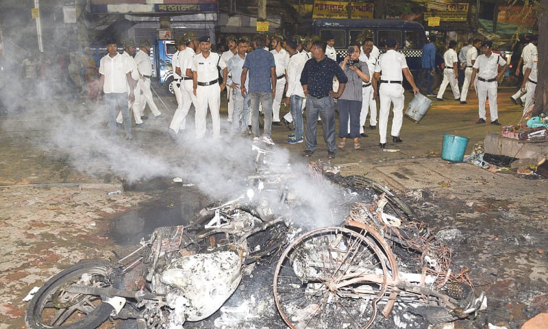 Kolkata: Police stand beside burning debris on a street following clashes during a rally held by Amit Shah, president of the ruling Bharatiya Janata Party.—AFP