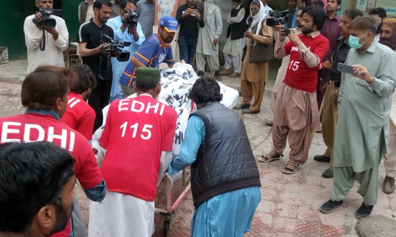 The body of a suspected militant is shifted following the joint operation. — DawnNewsTV