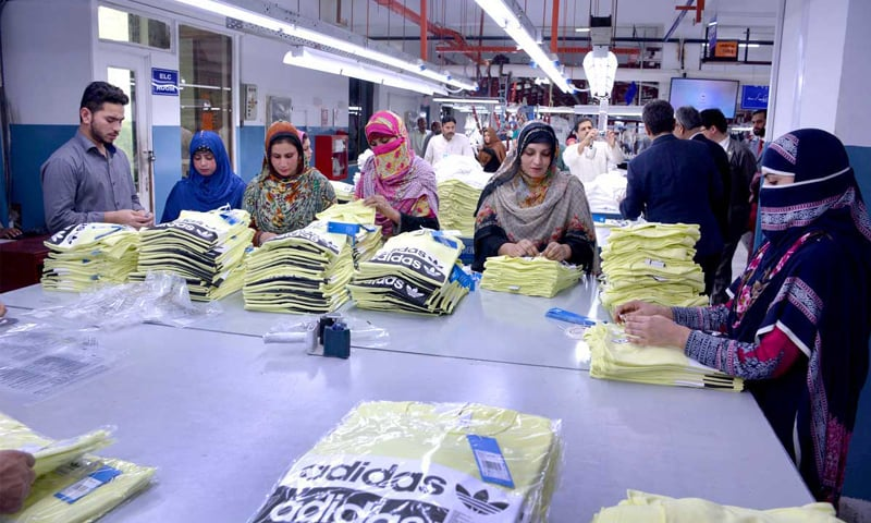 FAISALABAD: Workers pack export items at a garment factory on Thursday.—APP