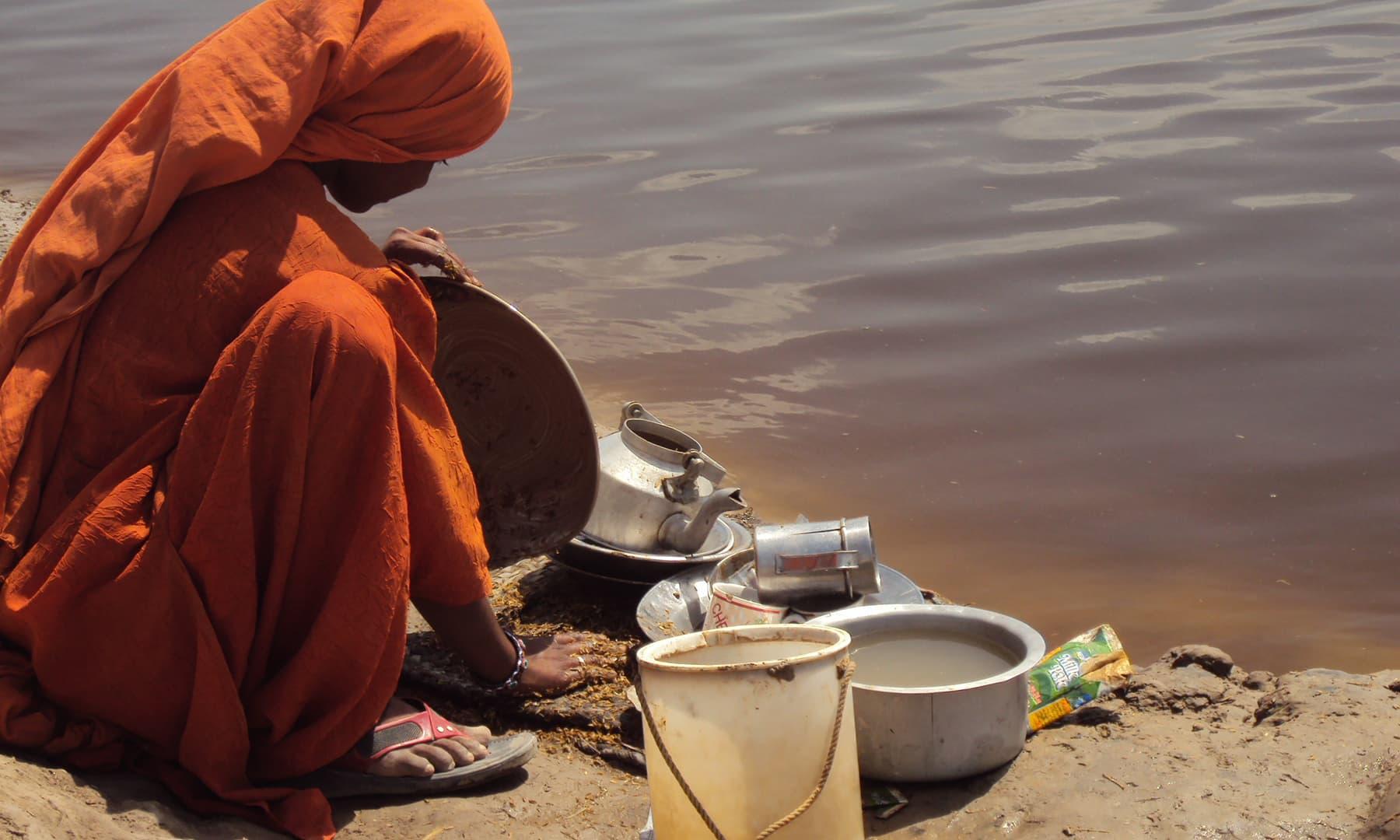 جن نالوں سے بچے پینے کے لیے پانی لے جاتے ہیں ان میں شگر ملز کے ڈسٹلری یونٹس کا اخراج شامل ہوتا ہے—تصویر ابوبکر شیخ