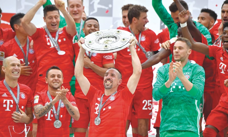 MUNICH: Bayern Munich's Franck Ribery (C) and team-mates celebrate with the Bundesliga trophy after they beat  Eintracht Frankfurt in the final match of the season at the Allianz Arena on Saturday.—AFP