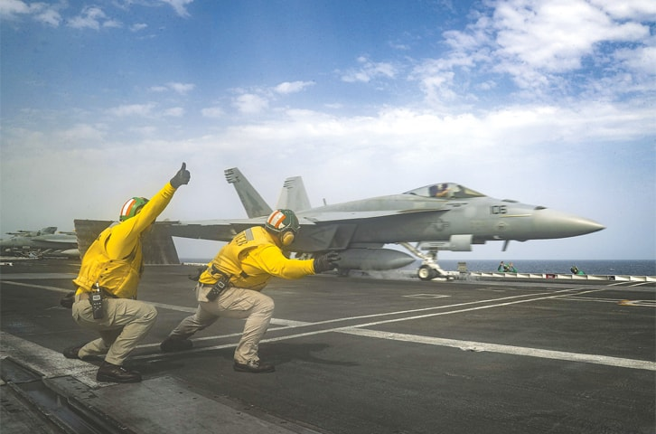 US Navy personnel launch an F-18 Super Hornet from the deck of the USS Abraham Lincoln aircraft carrier in the Arabian Sea.—AP
