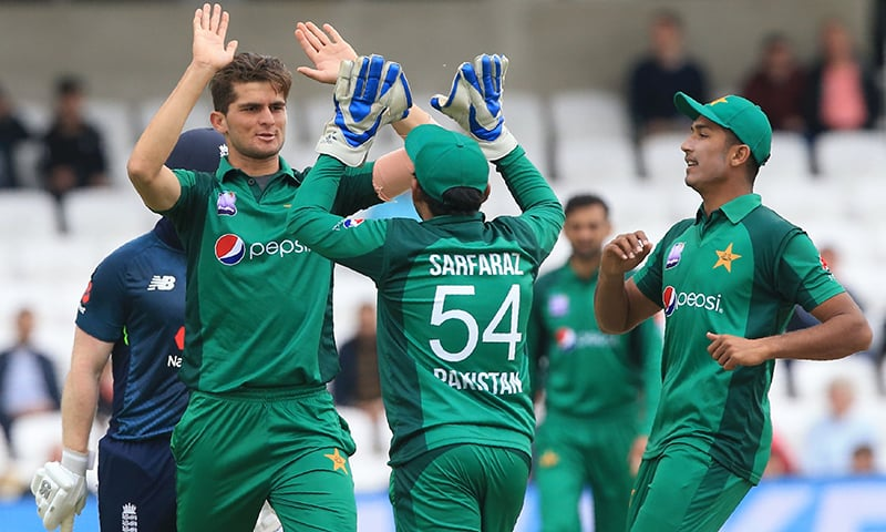 Shaheen Shah Afridi (L) celebrates with Sarfaraz Ahmed (C) after taking the wicket of England's Eoin Morgan. — AFP