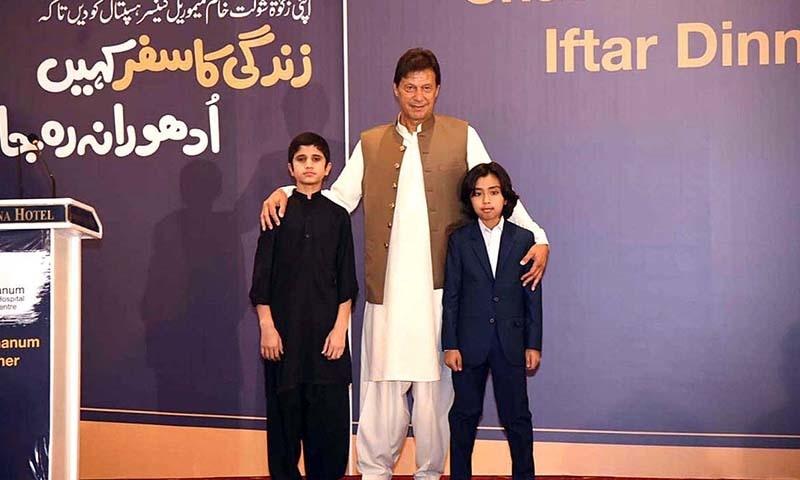 عمران خان شوکت خانم ہسپتال میں کینسر کا علاج حاصل کرنے والے 2 بچوں کے ساتھ کھڑے ہیں — فوٹو: اے پی پی