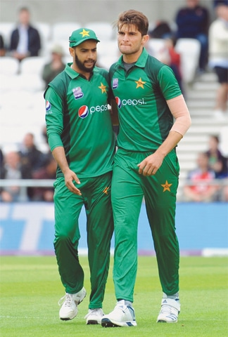 PAKISTAN paceman Shaheen Shah Afridi (R) celebrates with Imad Wasim after dismissing England's Chris Woakes on Sunday.—AP