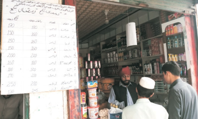 Customers at the shop of Gurmeet Singh in Jamrud. — Dawn