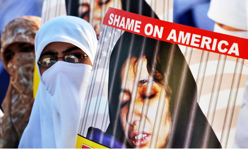 A supporter of Dr Aafia Siddiqui carries a poster size picture of the Pakistani scientist languishing in a US jail. — AFP/File