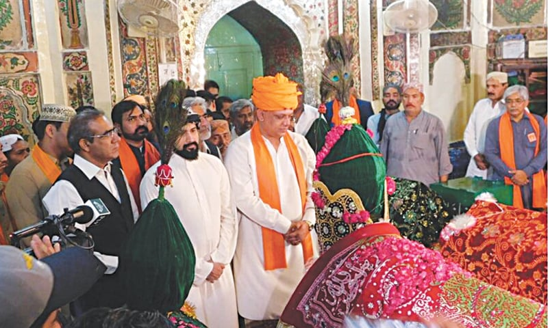 MINISTER for Auqaf Faraz Hussain Dero, along with custodian of the shrine and others, pays respects to Sufi saint Sachal Sarmast after laying a wreath on his grave in Daraza Sharif on Monday.—Dawn