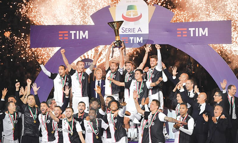 TURIN: Juventus players celebrate with the trophy after their Serie A match against Atalanta at the Allianz Stadium.—AFP