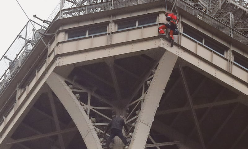 PARIS: A rescue worker (top in red) hangs from the Eiffel Tower while a climber is seen below him between two iron columns.—AP