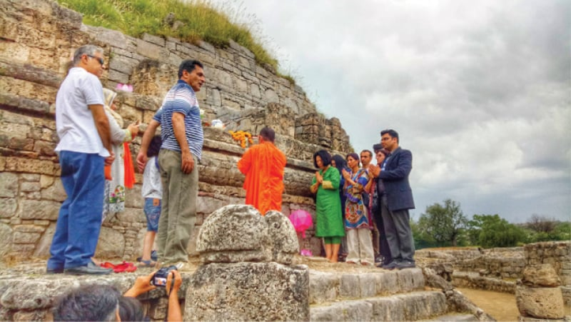 Participants perform rituals at the 3rd century BC Dharmarajika Stupa near Taxila in connection with Vesak Day. — Dawn